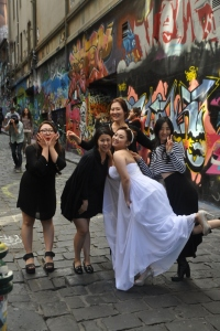 Bride on Hosier Lane taking pictures with her bridal crew