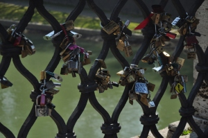 Locks attached to a bridge in Rome symbolizing a love connection.